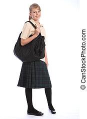 Teenage girl smiles wearing secondary school student uniform of tartan skirt and beige shirt, with big black shoulder bag.