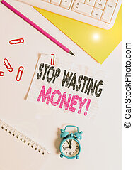 Text sign showing Stop Wasting Money. Conceptual photo advicing demonstrating to start saving and use it wisely Flat lay above white blank paper with copy space for text messages.