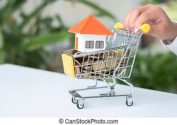 The hand is pushing the cart.Orange roof house and coins in a wheelchair. House trading ideas Saving money to buy a family home Real estate investment, mortgage. Shopping requires a lot of money.