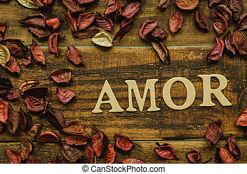 """The word """"Amor"""" on a rustic wooden with dry red petals around"""