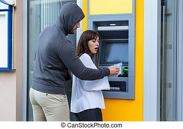 Thief Stealing Card From Woman Standing Near The Cash Machine