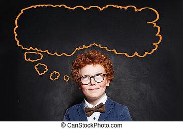 Thinking schoolboy and big empty speech cloud bubble on chalkboard background