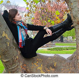 Thinking woman relaxing on tree and looking up with smiling on autumn color