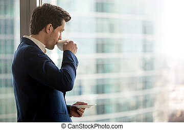 Thoughtful businessman drinking coffee, looking through office w