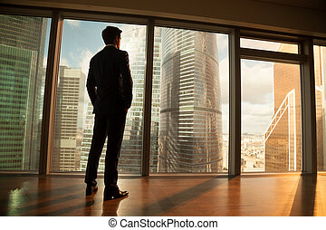 Thoughtful businessman looking out of big window at sunset city