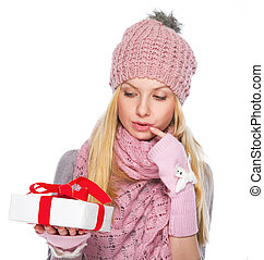 Thoughtful girl in winter clothes looking on christmas present box
