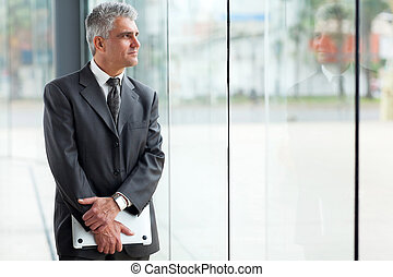 mid age businessman looking through office window