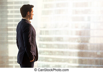 Thoughtful successful businessman looking at city standing in of