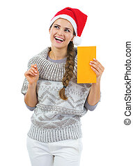 Thoughtful young woman in sweater and christmas hat holding letter
