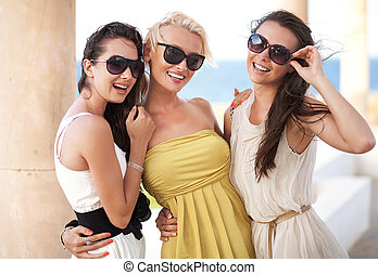 Three adorable women wearing sunglasses