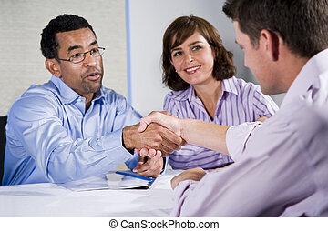 Three business people meeting, men shaking hands