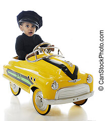 A toddler cab driver wering a cabbie hat and driving a yellow pedal-car taxi. On a white background.