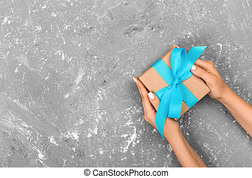 Top view female hands holding gift box on grey background with space for text