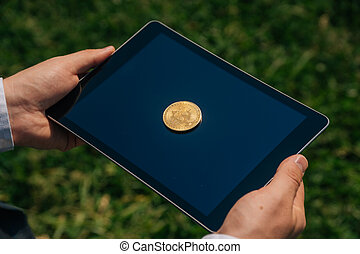 Top view of bitcon cryptocurrency lies on digital tablet. Virtual money or coin close up sign