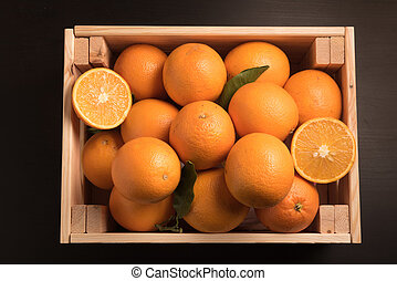 top view of Ripe sweet orange in wooden box isolated on black background