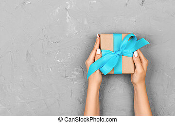 Top view woman hands holding present box with blue bow on gray background with copy space