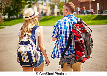 Young man and woman in casualwear traveling in foreign city