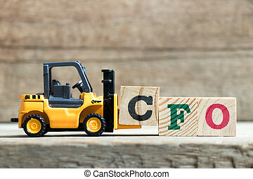 Toy yellow forklift hold letter block C to complete word CFO (Abbreviation of Chief Financial Officer) on wood background