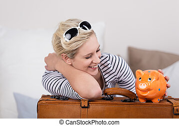 Trendy traveler with a piggy bank