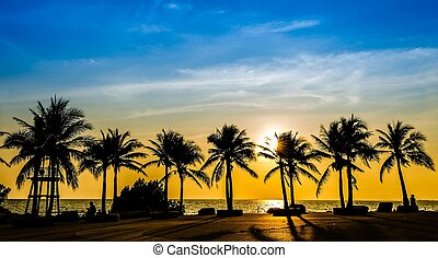 Tropical beach with coconut palm on sunset background