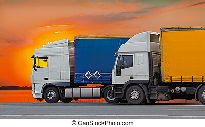 Trucks move along the highway against the red sunset sky