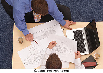 Aerial view of two businessmen in a corporate setting going over the blueprint details.