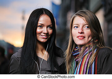 Two beautiful girls on a street at sunset. Shallow DOF, focus on brunette girl.