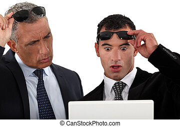 two businessmen looking at their laptop very surprised