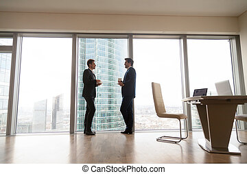 Two businessmen standing at full-length window in office, coffee