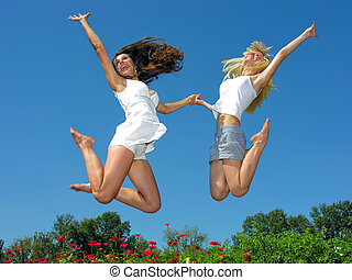 two cheerful girlfriends jumping outdoors
