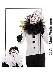 two clowns in a frame with a yellow flower