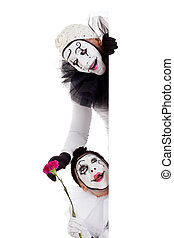 two clowns in love looking around a border