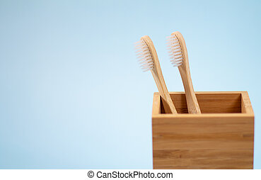 Two eco-friendly bamboo toothbrushes in wooden holder on light blue background with space for text
