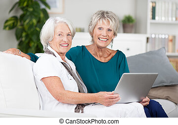 Two elderly ladies sharing a laptop computer