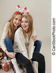 two funny girls on the sled with gifts
