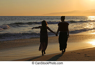 Two Girls Holding Hands at a California Beach at Sunset.