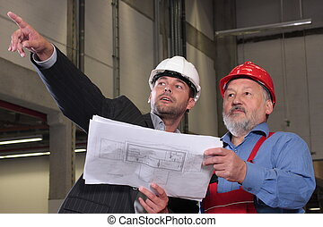 two man reviewing blueprints, talking about project