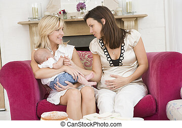 Two mothers in living room with baby and cake smiling