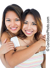 Two pretty sisters embracing in front of the camera