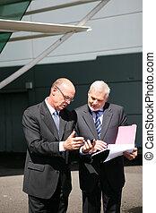 Two senior businessmen going over paperwork outdoors