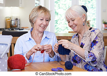Two Senior Female Friends Knitting At Home Together