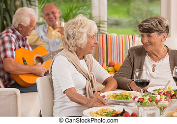 Two senior women talking and drinking wine