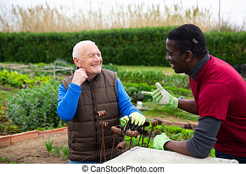 Two smiling gardeners talking together in garden
