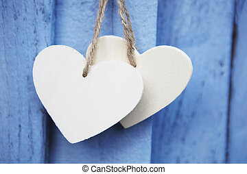 Two Wooden Hearts Hanging On Blue Wooden Surface