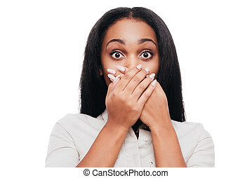 Unbelievable news! Shocked young African woman covering mouth with hands and looking at camera while standing against white background