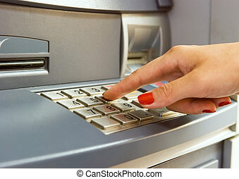 Woman's hand dialing pin on bank ATM keyboard