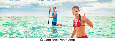 Vacation fun summer sport activity leisure beach watersport couple paddleboarding in ocean banner panorama. Paddleboard people on stand-up paddle boards on Hawaii . Mixed race woman Caucasian man