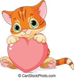 Cute little kitten holding Love Heart