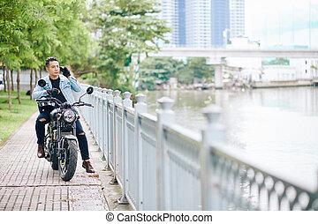 Vietnamese man sitting on motorcycle
