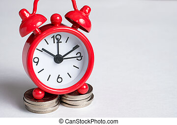 Vintage red clock on on a stack of coins a white background left side. Place for text.